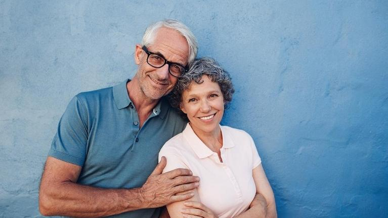 older couple with blue background smiling l dentist near me austin tx